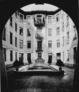 """Widok z przejazdu bramnego na podwórko w roku 1905. Oddajmy głos dziennikarzowi """"Przeglądu Technicznego"""" z roku 1905. """"Podwórze ma kształt prawidłowy, w dwóch jego rogach na całą wysokość domu dano dwie nisze, w których mamy duże okna z balkonami przy pokojach stołowych i małe okna z łazienek i waterklozetów. Na takie pomysłowe opracowanie tej części domu mieszkalnego zwracamy szczególniejszą uwagę, gdyż, o ile wiemy, dotychczas w Warszawie nie było zastosowane. Na środku podwórza duży zbiornik z wodotryskiem, wyłożony płytkami niebieskiemi. które, będąc pokryte wodą, wywołują wrażenie malownicze. Całe podwórze wyłożono płytkami terrakotowemi wzorzystemi."""""""