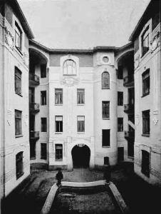 """Widok z podwórka na przejazd bramny w roku 1905. Opis za """"Przeglądem Technicznym"""" z roku 1905. """"Lice podwórzowi opracowano także architektonicznie w stylu secesyjnym: gzyms główny bez żadnych ozdób, traktowany konstrukcyjnie, z żelaza teowego i z płytek terrakotowych barwy zielonej i granatowej; takiemi samemi płytkami wyłożono i część ściany nad oknami piętra trzeciego. Między oknami piętra pierwszego i drugiego stoją kanelowane pilastry, zakończone tarczami słonecznemi"""""""
