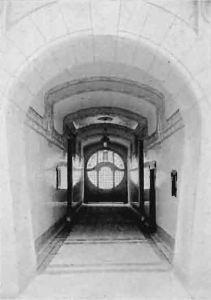 """Widok przejazdu bramnego w 1905 roku. """"Wnętrze bramy również opracowano nie szablonowo; nie ma tu gzymsów, bogatych sztukateryi i t. p. Natomiast ściany wyłożono gładkiemi płytkami fajansowemi barwy białej, a gładkie sklepienie podzielono na 4 pola do obrazów""""."""