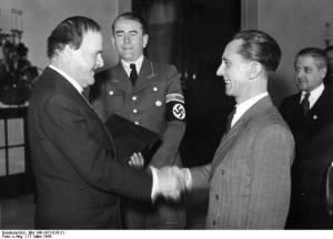 Wilhelm Kreis (z lewej, w marynarce) przyjmuje z rąk Goebbelsa nominację na generalnego radcę budowlanego niemieckich cmentarzy wojennych. Przy nim (w mundurze) Albert Speer.