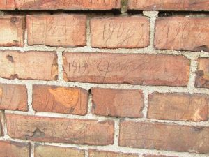 Daty i podpisy na murze.