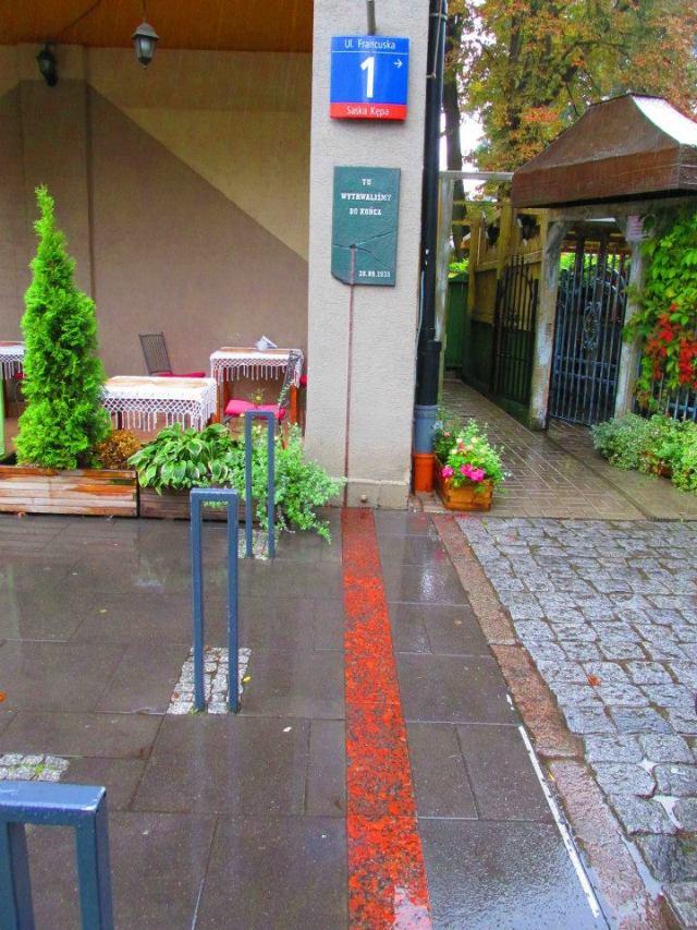 Miejsce w którym przebiegała barykada oznaczono na chodniku.