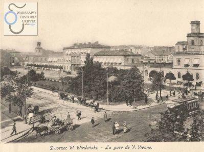 """Skrzyżowanie Alej Jerozolimskich i Marszałkowskiej. Widok na Dworzec Wiedeński. Dworzec, wzniesiony według projektu Henryka Marconiego, w założeniu miał przypominać dwa parowozowy, stojące do siebie """"plecami"""".. Budowę ukończono 14 czerwca 1845 roku."""