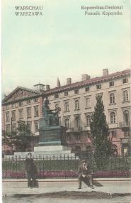 Pomnik Mikołaja Kopernika z Domem Interesów Andrzeja Zamoyskiego w tle. Budynek wzniesiono w latach 1843-1846 według projektu Henryka Marconiego jako neorenesansową kamienicę dochodową. Płaskorzeźbami ozdobił ją Paweł Maliński.