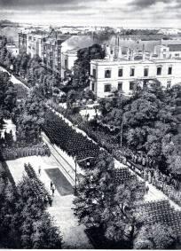 5 października 1939 roku, w Alejach Ujazdowskich, Adolf Hitler odebrał defiladę zwycięskiej armii niemieckiej. Jest wiele zdjęć z tej, dla Polaków smutnej, ceremonii. Prezentowana fotografia jest szczególnie interesująca, gdyż została wykonane z góry, najprawdopodobniej z okna nieistniejącej dziś kamienicy Spokornego. Dzięki temu, że fotograf znalazł się wysoko, widać doskonale pałacyk Rembielińskiego przy ulicy Piusa XI (obecnie nosi nazwę Piękna) i stojącą za nim kamienicę Taubenhausa. Wypalone mury kamienicy zostały rozebrane po wojnie. Dalej widoczne kamienice również wojny nie przetrwały. Podczas spacerów Alejami Ujazdowskimi, pokazujemy naszym Gościom miejsce, z którego Hitler przyjmował defiladę.