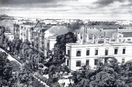 5 października 1939 roku, w Alejach Ujazdowskich, Adolf Hitler odebrał defiladę zwycięskiej armii niemieckiej. Jest wiele zdjęć z tej, dla Polaków smutnej, ceremonii. Prezentowana fotografia jest szczególnie interesująca, gdyż została wykonane z góry, najprawdopodobniej z okna nieistniejącej dziś kamienicy Spokornego. Dzięki temu, że fotograf znalazł się wysoko, widać doskonale pałacyk Rembielińskiego przy ulicy Piusa XI (obecnie nosi nazwę Piękna) i stojącą za nim kamienicę Taubenhausa. Wypalone mury kamienicy zostały rozebrane po wojnie. Dalej widoczne kamienice również wojny nie przetrwały. Podczas spacerów Alejami Ujazdowskimi, pokazujemy naszym Gościom miejsce, z którego Hitler przyjmował defiladę