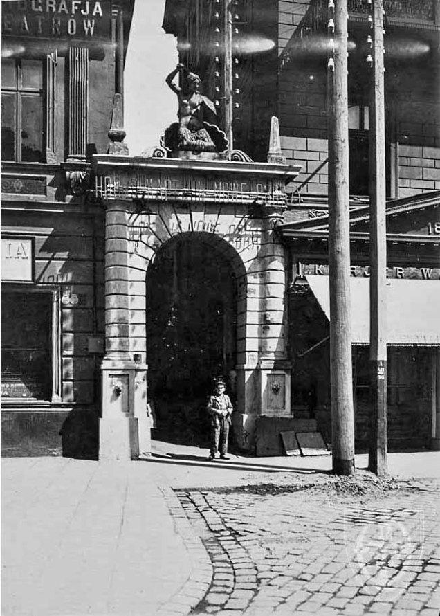 Siostra Syrenki z Rynku Starego Miasta na szczycie bramy-zdroju zamykającego ulicę Karową.